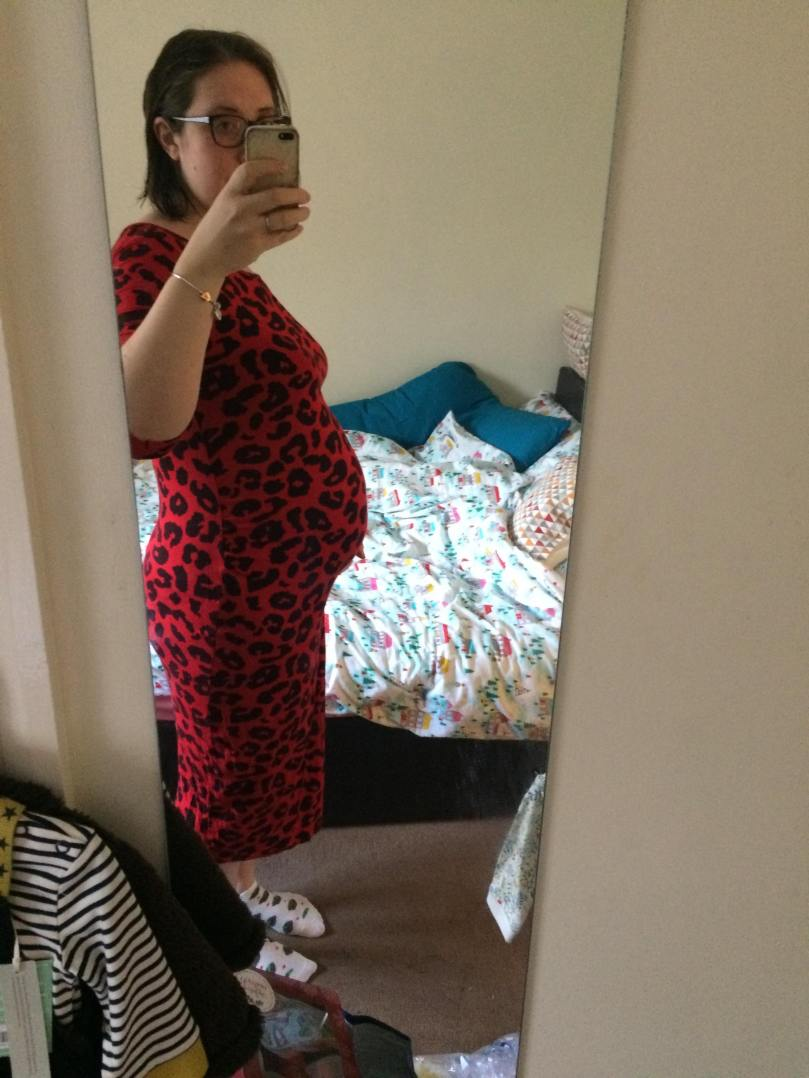 Hayley standing with a 30 week bump, in front of a very messy unmade bed.
